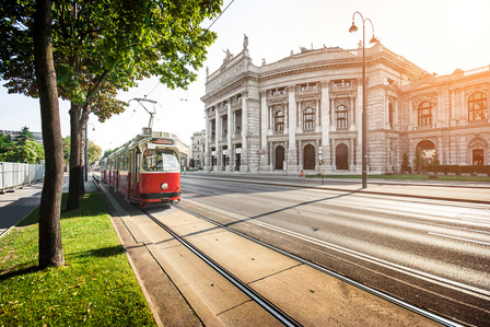 Beautiful view of famous Wiener Ringstrasse with historic Burgtheater (Imperial Court Theatre) and traditional red electric tram at sunset in Vienna, Austria