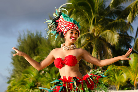 COOK ISLANDS Portrait of Polynesian Pacific Island Tahitian female dancer in colorful costume dancing on tropical beach with palm trees in the background.