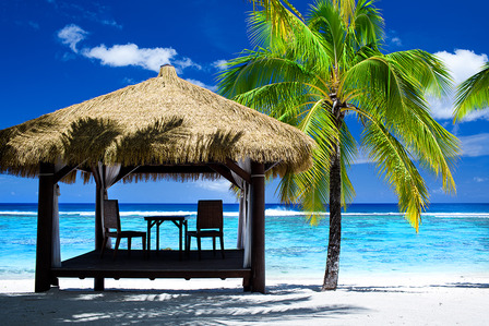 COOK ISLANDS Tropical gazebo with chairs on amazing beach with palm tree