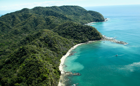 COSTA-RICA Lush jungle covered mountains stretch out into the Gulf of Nicoya next to the rocky and sandy beach of Ballena Bay in Costa Rica.