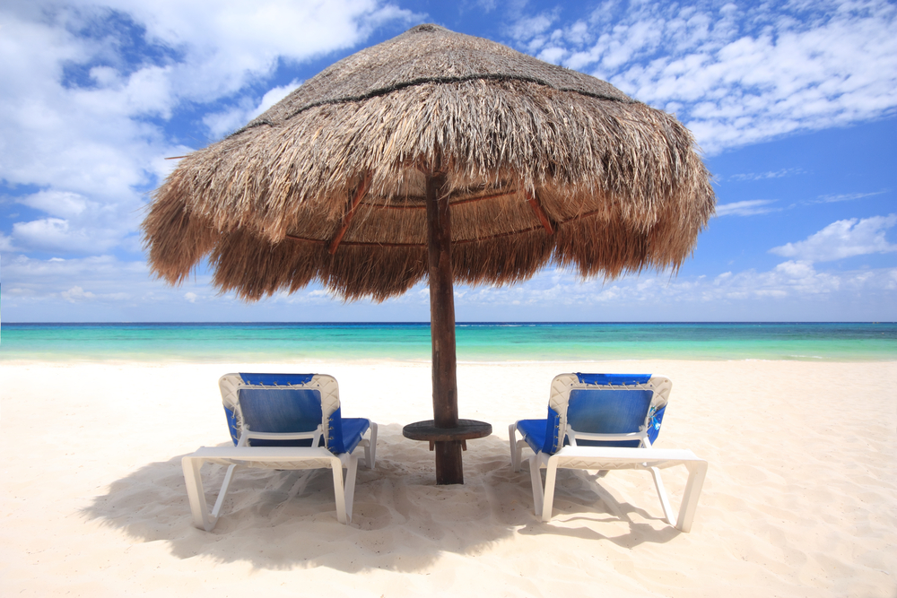 Beach chairs under thatched umbrella overlooking a tropical beach, Cozumel