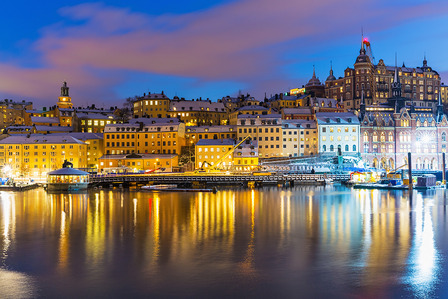 SWEDEN-Beautiful winter night snowy scenery of Slussen district of the Old Town (Gamla Stan) in Stockholm, Sweden